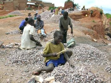 A boy breaks stones into gravel in Kampala.